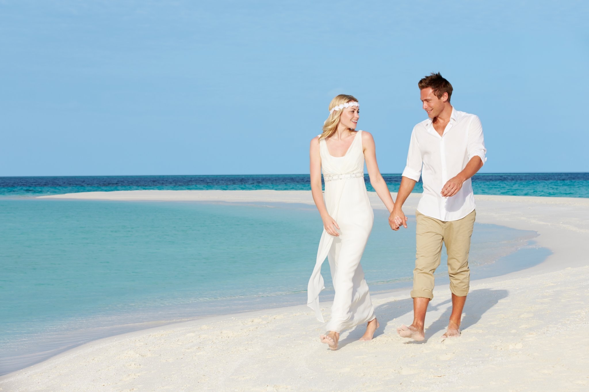Couple At Beautiful Beach Wedding Walking Along Sand Spit Holding Hands